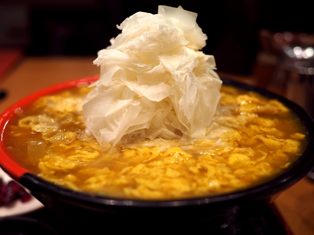 2種類のカレー出汁が2層構造になった鶏卵カレーうどんに名物の0.01mmのふわふわチーズをトッピング! 梅田 「極楽うどん TKU ルクア大阪店」